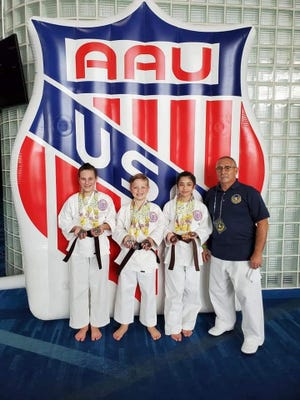 Rion Nogel, Brevin Nogel and Kaitlyn Hatchell are shown with sensei Ismael Munoz.