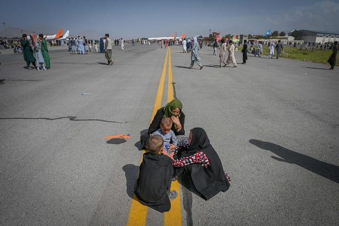 Afghan people sit along the tarmac as they wait to leave the Kabul airport in Kabul on August 16, 2021, after a stunningly swift end to Afghanistan's 20-year war, as thousands of people mobbed the city's airport trying to flee the group's feared hardline brand of Islamist rule. (Wakil Kohsar/AFP via Getty Images/TNS)