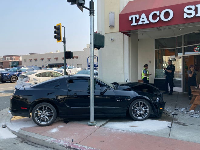 This black Ford Mustang crashed into the pillar of the Cascade Square building in downtown Redding after colliding with the White Toyota Prius in the background, police said. The collision occurred on Tuesday, Aug. 24, 2021.