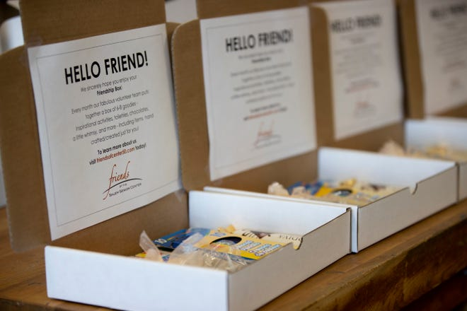 Volunteers prepare friendship boxes filled with games and treats for seniors at Center 50+ in Salem, Oregon on Tuesday, Aug. 24, 2021.