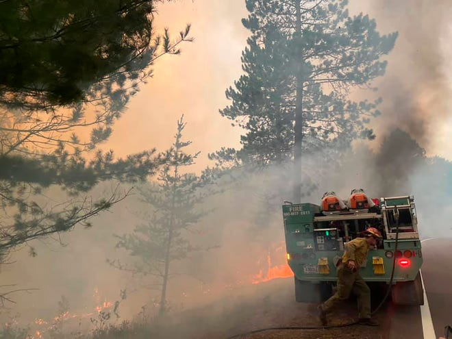 In this photo provided by the United States Forest Service, firefighters battle a wildfire, Monday, Aug. 23, 2021, near Greenwood Lake in the Superior National Forest of northeastern Minnesota. The fire has burned more than 14 square miles and promoted a new round of evacuations of homes and cabins on Monday. (United States Forest Service via AP)