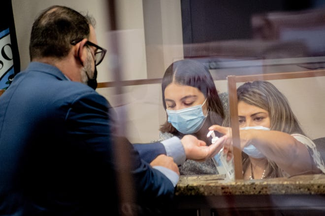 District 1 city Rep. Peter Svarzbein, left, asks District 3 city Rep. Cassandra Hernandez for hand sanitizer Tuesday during the first in-person City Council meeting since the beginning of the COVID-19 pandemic.