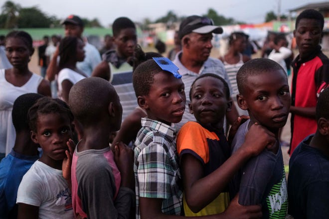 Children line up to receive food brought by a private citizen to the refugee camp in Les Cayes, Haiti, on Aug. 23.
