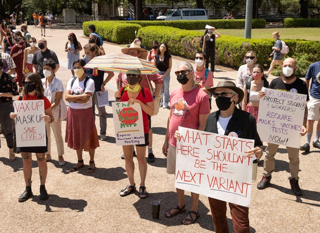 Anthropology Department Chair Anthony Di Fiore, right, holds a sign during a rally Wednesday at the University of Texas to demand UT leaders require masks on campus, among other measures to curb the spread of COVID-19.
