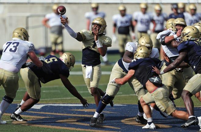 Akron Zips quarterback Kato Nelson, center, makes a pass under pressure during football practice, Wednesday, Aug. 25, 2021, in Akron, Ohio.