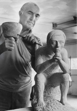 Akron sculptor Cory Fiocca works on a sandstone sculpture in August 1971 at his Sackett Hills Drive home.