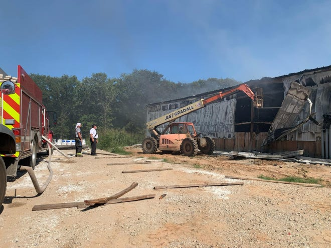 A section of a metal building is removed to give firefighters better access to the structure near Thackerville Tuesday, Aug. 24, 2021.