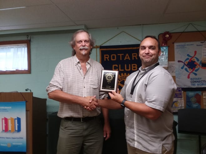 Citizen of the year Tom Neel accepts his plaque from Rotary President Brad Romano