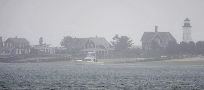 Shrouded by mist, Sandy Neck Lighthouse offers little guidance for a charter fishing boat heading back into Barnstable Harbor as the remains of Tropical Storm Henri cloud over Cape Cod skies.
