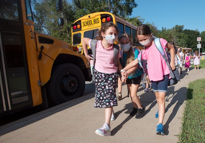 Students hold hands as they enter Blackhawk Intermediate School on the first day of classes Tuesday in Chippewa Township.