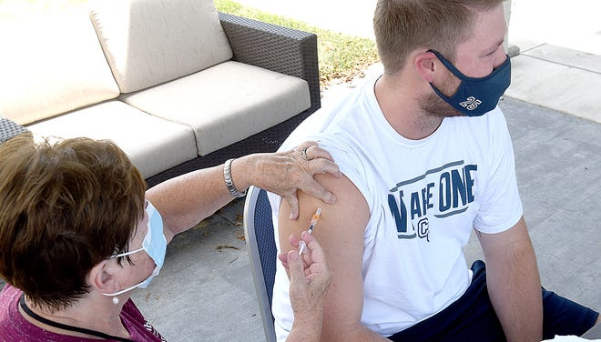 Hazel Kerr, registered nurse with Columbia/Boone County Public Health and Human Services, gives Mark Haire, a graduate assistant at Columbia College, a COVID-19 vaccine shot on Wednesday at Columbia College. Nine people received vaccinations.