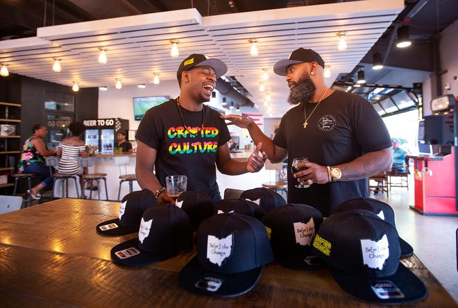 """Anthony """"Sizzle"""" Perry Jr. and Rahim Ewan with the new hats that the two Gahanna natives are selling at Crafted Culture Brewing as a fundraiser to put money back into their community."""