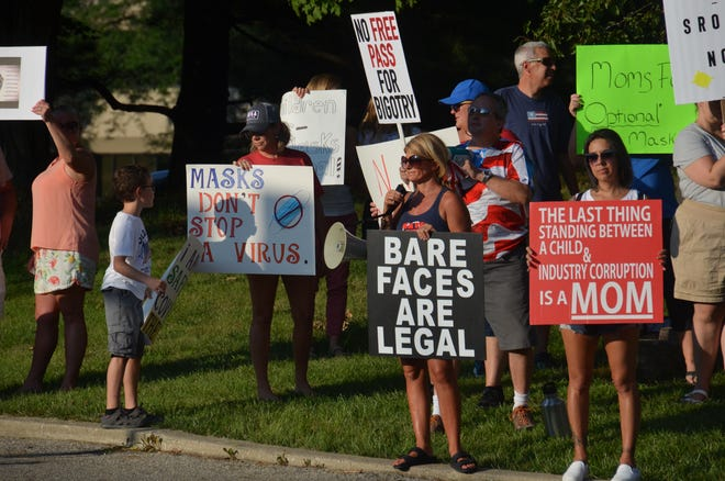 Demonstrators opposed to a districtwide mask mandate in Worthington schools hold signs outside the Worthington Education Center before the school board meeting Aug. 23.