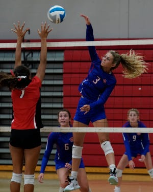 Lenawee Christian's Isabelle Kirkendall goes up for a kill while Addison's Mia Nejelski tries to block during Tuesday's match at Addison. [Telegram photo by Mike Dickie]