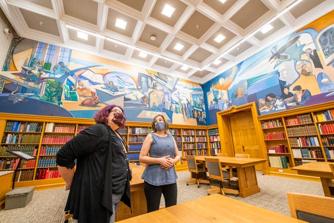 Rebecca Baumann, left, head of public services for Indiana University's Lilly Library, and Diane Dallis-Comentale, interim dean of IU libraries, discuss the new mural Wednesday at the recently renovated Lilly Library.