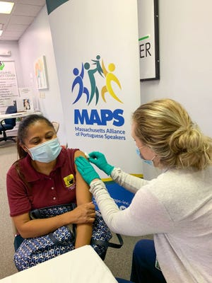 A woman receives the Covid-19 shot at a recent vaccination clinic organized by the Massachusetts Alliance of Portuguese Speakers (MAPS).