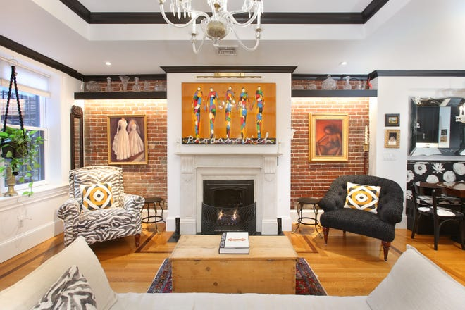 Unit 2 at 88 Beacon St. on Beacon Hill was for sale earlier in the year. This one-bedroom home has a lot of fine features, including exposed brick that surrounds the gas fireplace. The picture above the fireplace is hinged and conceals a flat screen TV.