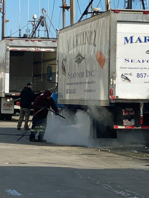 This truck is getting a good cleaning to get ready for the next load of fish on the Boston Fish Pier.