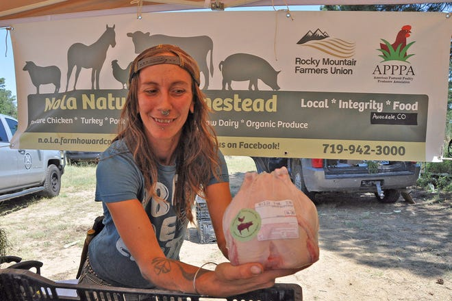 Nick Wagner of Nola Naturals holds up her farm's specialty product, frozen whole chicken, inside a booth at the Colorado Farm and Art Market in Colorado Springs. She and her husband, Josh, plan to raise up to 6,500 birds on land they recently purchased near Avondale. They received a state grant to help install a poultry-processing unit at the farm.