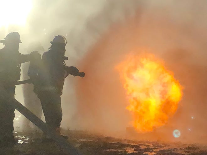 A team of Southeastern Colorado firefighters work to extinguish a fire on a piece of t-shaped equipment meant to simulate a natural gas pipeline rupture fire in La Junta, Colo., on Wednesday, Aug. 24, 2021.