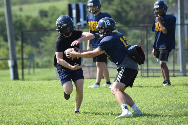 Senior wide receiver Devin Stutz takes a handoff from sophomore quarterback Cooper Beying during Pleasant Ridge's football practice.