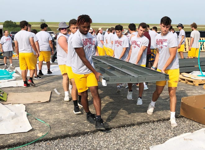 How many members of the St. John Fisher College football team does it take to move playground equipment into place? Lots of them, as demonstrated during a work day at the Inclusion in Motion playground in the town of Canandaigua.