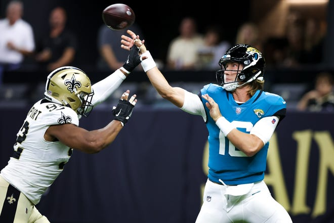 Jacksonville quarterback Trevor Lawrence, right, gets a pass away before being hit by New Orleans defensive end Marcus Davenport. On Wednesday, Lawrence was announced as the Jaguars' starting quarterback for the regular season opener.