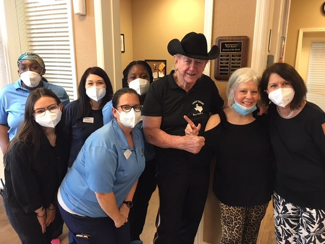 Former professional wrestler Dory Funk Jr., center, wearing hat, and his wife, Marti, at his immediate left, pose with members of the Brentwood at Fore Ranch care staff. From left: Edmanni Johnson, Hazel Kazee, Leila Kazee, Jenn Vetter, Teaya Braithwaite and Ginny Vinson at far right.