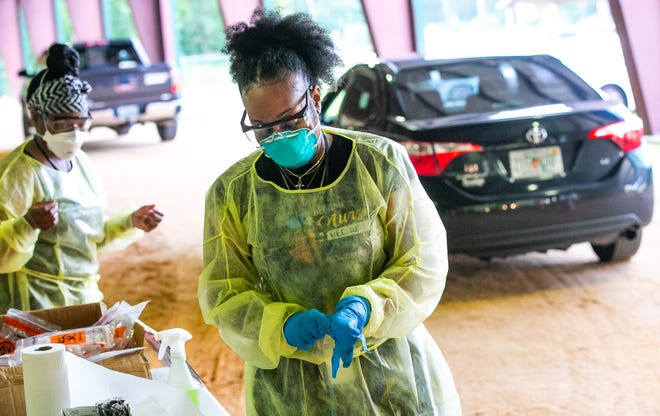 Tnacia Stivers, an LPN, gloves up to test another person Wednesday morning at the Southeastern Livestock Pavilion in Ocala.