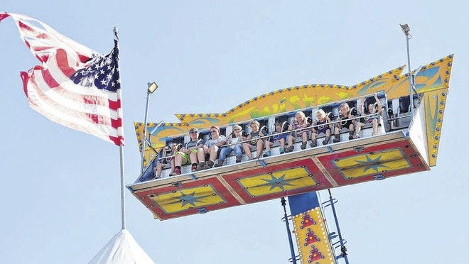 Youngsters are 'flag-high' as they ride the Twister during an earlier year's Emmet-Charlevoix County Fair.