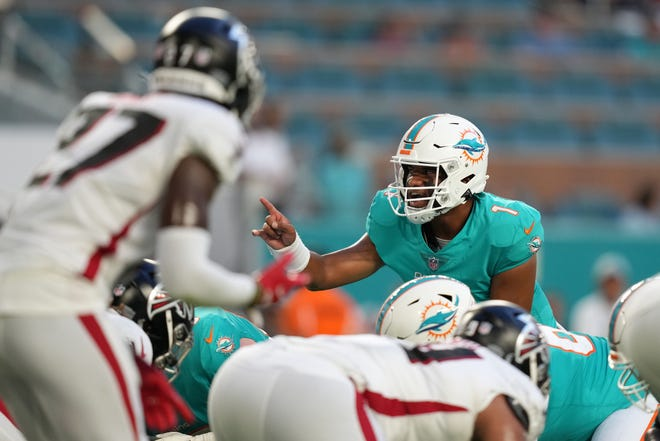 Aug 21, 2021; Miami Gardens, Florida, USA; Miami Dolphins quarterback Tua Tagovailoa (1) gestures at the line during the first half against the Atlanta Falcons at Hard Rock Stadium. Mandatory Credit: Jasen Vinlove-USA TODAY Sports