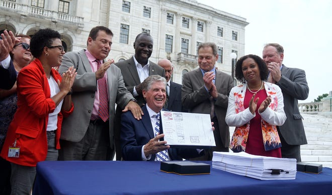 Surrounded by members of the Rhode Island House and Senate who helped craft it, Gov. Dan McKee holds up the newly signed state budget last month.
