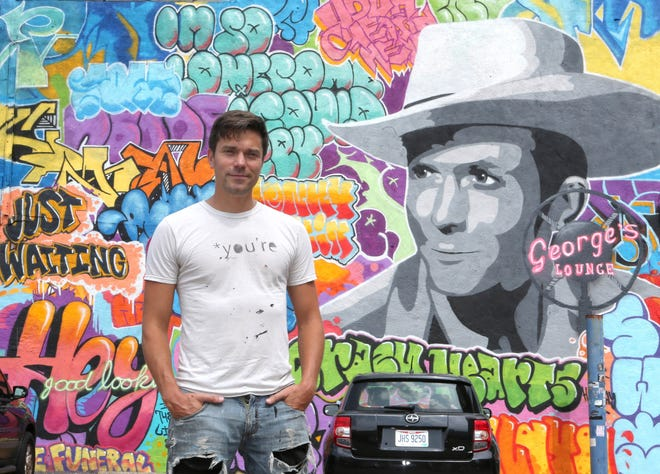 Artist Tim Carmany is shown next to the mural he created outside of George's Lounge in downtown Canton. He also received assistance from three other artists who specialize in graffiti-style, street art. George's Lounge is at 315 Cleveland Ave. NW.