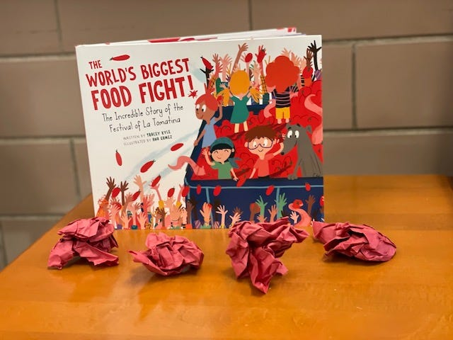 Examples of students' paper tomatoes and a picture book about the festival.
