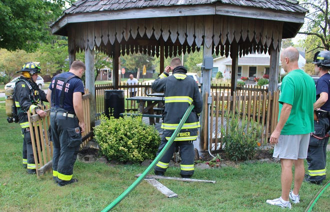Martinsville Parks Superintendent Keenan Steinway, wearing green, looks on as the Martinsville Fire Department works to extinguish a small fire at the gazebo at Doris Daily Park on Tuesday.
