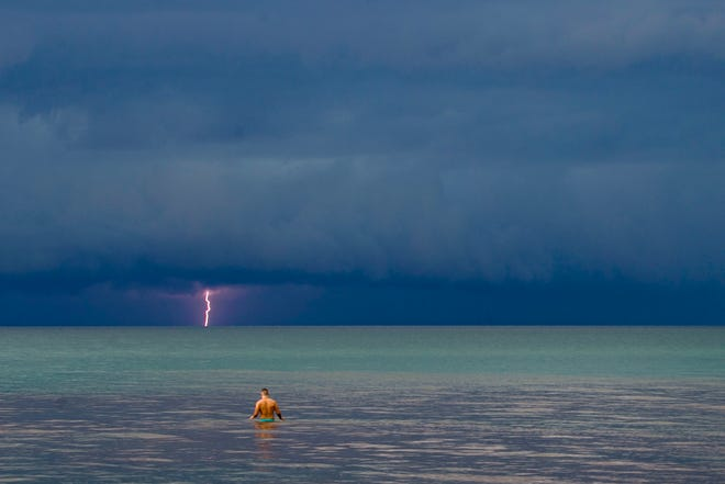 A person wades in the water as a storm rolls in over Lake Michigan on Tuesday in Chikaming Township, Michigan. Extreme heat and chances for more thunderstorms will remain with us through the weekend.