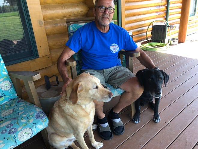 Gary Hay sits on his front porch with friends and work companions Eddie, left, and Virgil. Eddie recently retired as a search dog with the Federal Emergency Management Agency.