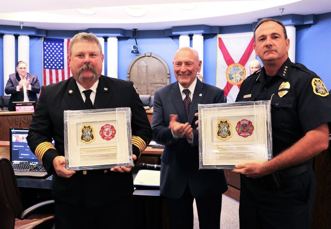 Venice Fire Chief Shawn Carvey, left, and Venice Police Chief Tom Mattmuller, right, flank Venice City Manager Ed Lavallee Tuesday morning and show off special shadow boxes Lavallee had made for both men to highlight the cooperation between the two departments. Carvey will retires Sept. 1, while Mattmuller plans to retire in December.