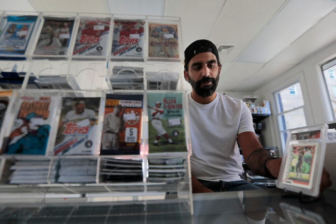 Brandon Santiago, co-owner, grabs a card that he just traded from a customer at the newly opened The Kard Shop on Pleasant Street in New Bedford.