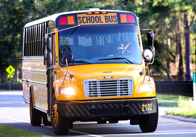 An Alachua County Public Schools bus driver turns a bus out of Eastside High School in Gainesville Fla. Aug. 24, 2021.