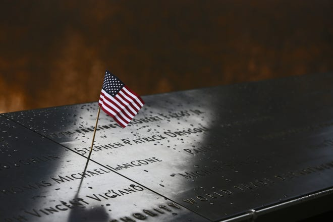 A small American flag sits atop the name of Stephen Patrick Driscoll, one of thousands of names engraved on the 9/11 Memorial in lower Manhattan.