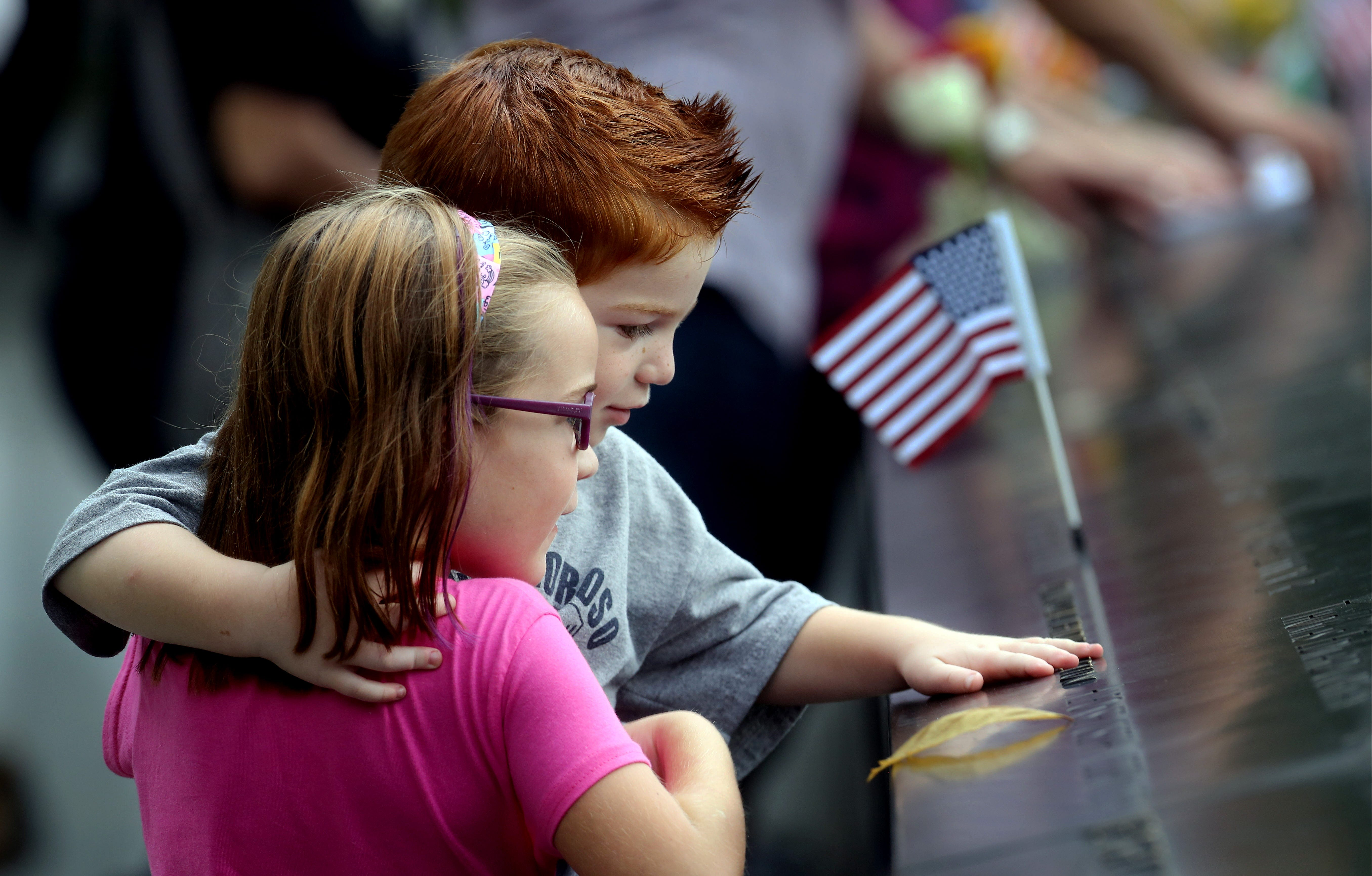 During a ceremony marking the 15th anniversary of the Sept. 11 attacks, Lucy Smith, 6, and her brother Ryan, 2, of New Jersey, look at the name of their uncle, Port Authority Police Officer Chris Amoroso, who was killed in the attacks on the World Trade Center.