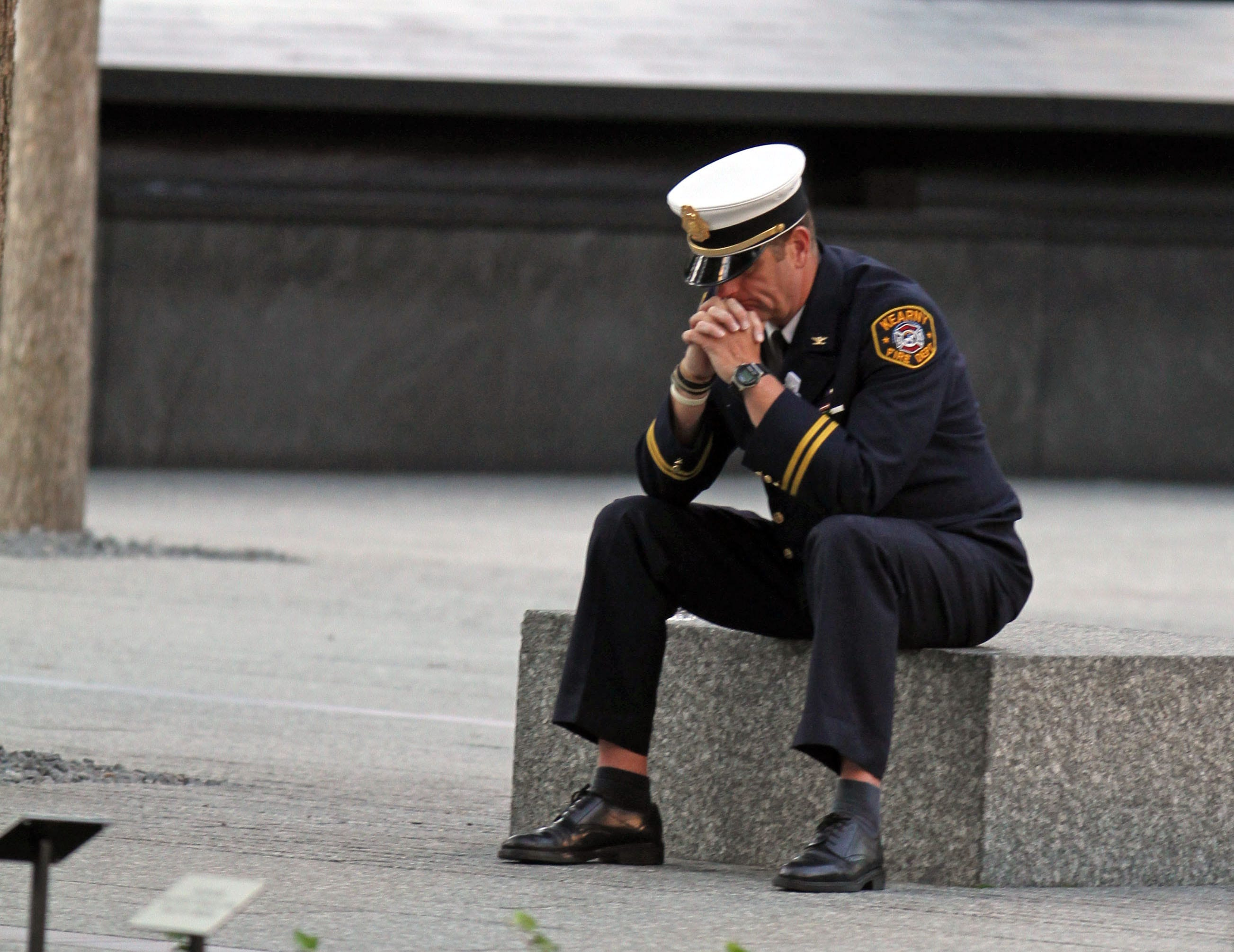 A firefighter sits in the plaza at the World Trade Center site in Lower Manhattan before the annual 9/11 ceremony Sept. 11, 2012.