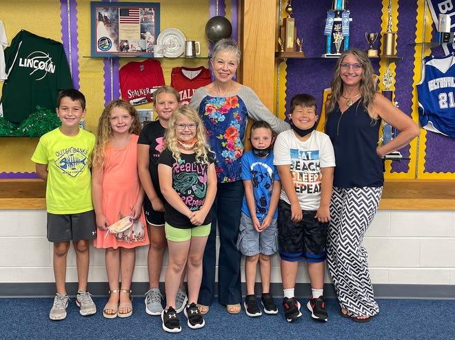 Lisa Mowery alongside fellow secretary Karen Hobson pose with Shawswick Elementary School students in front of a memorabilia display in the school's front office.