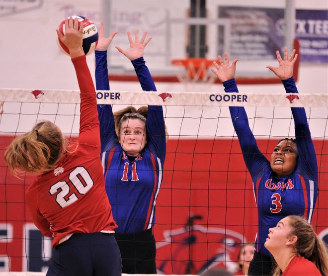 Cooper's Ana Tetaj (11) and Emani Davis (3) defend at the net as Jim Ned's Keeli Stockton (20) hits the ball in the first set.