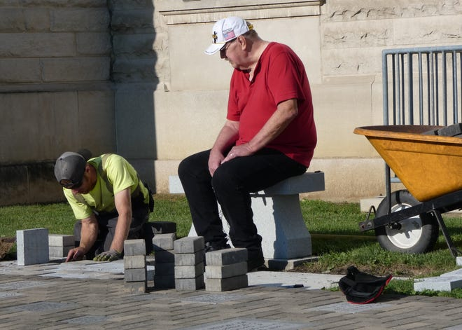 Don Scheererof the Crawford County Veterans Hall of Fame, right, watches asJustin Blocker ofOberlander's Tree and Landscape installs a special section of memorial pavers.