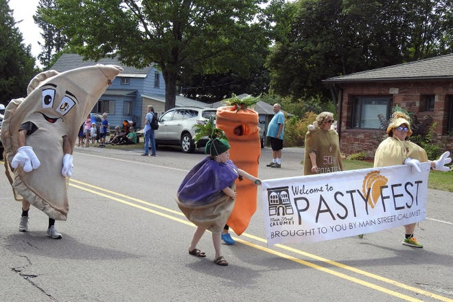 People in pasty costumes march, Saturday, Aug. 21, 2021, during the pasty festival in Calumet, Mich., an event that was canceled in 2020 because of the coronavirus. Pasties, typically meat and potatoes wrapped in a crust, are a famous food in Michigan's Upper Peninsula.