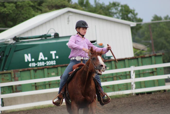 Samantha Young, 12, riding her 24-year-old horse Whattahotrodandhoney, picks up a stake in the barrel race event Wednesday at the Sandusky County Fair.