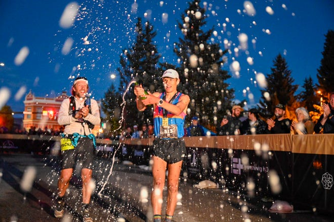 Adrian Macdonald, 32, of Fort Collins, Colo., pops the cork on a bottle of champagne after winning the Leadville Trail 100 on Saturday, Aug. 21, 2021, in Leadville, Colo. Macdonald's winning time of 16 hours, 18 minutes and 19 seconds was the fifth-fastest in the race's 38-yeare history.