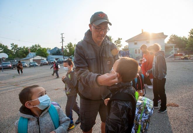 William Bloyd helps adjust the mask on his son Cameron on the first day of school at Whittier Elementary School, Wednesday morning.